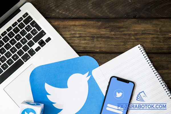 на столе стоит ноутбук и смартфон с логотипом Твиттер