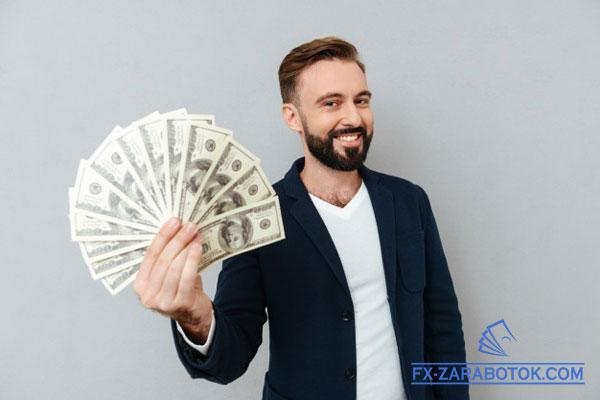 парень держит доллары в виде веера