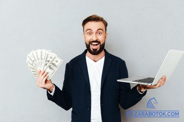 парень с ноутбуком и долларами