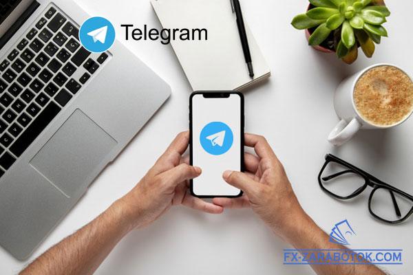 в руках держит телефон с логотипом Телеграм